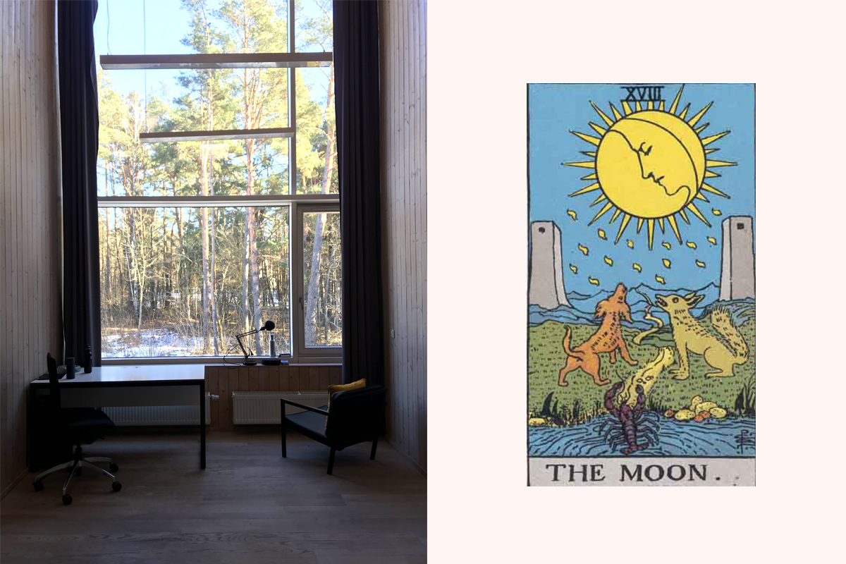A desk and two chairs in front of a tall window, looking out into snow and pines, next to The Moon tarot card