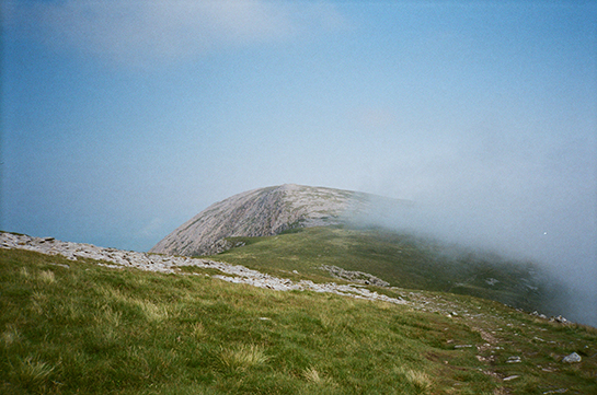 The top of a mountain in Wales, with low clouds wafting over the grass