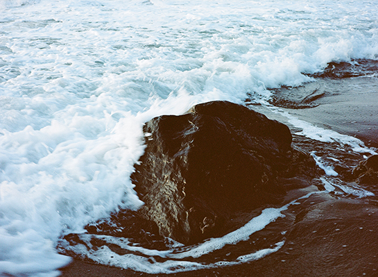 A wave breaking around a rock on a black sand beach