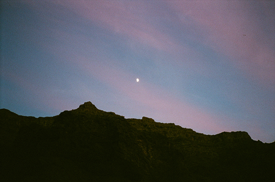 A rocky ridgeline silhouetted against a pink and blue evening sky featuring a gibbous moon