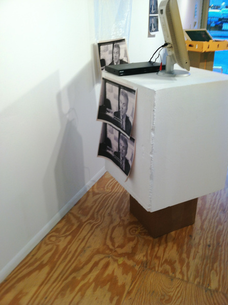 Monitor, styrofoam block, found packaging, inkjet on newsprint, box fan, plastic. 2014