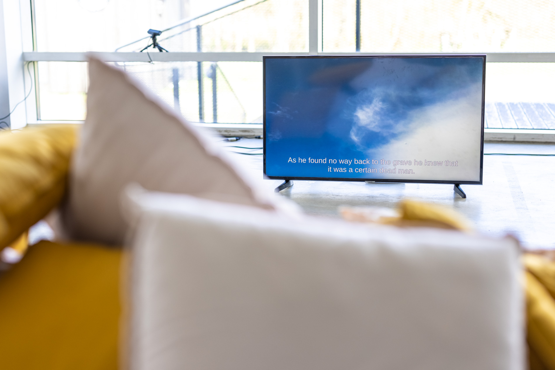 """A TV screen in a gallery space showing a live video feed of the sky above. The sky is mainly blue with some wispy clouds. The video is captioned with a sentence that begins with """"As he found no way back…""""."""