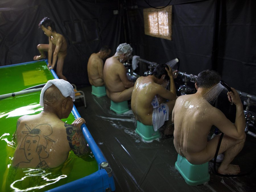 sixty-nine-year-old-and-tattooed-toyoo-ide-left-bathes-with-fellow-evacuees-in-a-traditional-japanese-style-bath-set-up-in-a-tent-by-japans-self-defense-forces-at-an-evacuation-center-in-koriyama-japan-theres-no-water-or-electricity-now-but-if-there-were-