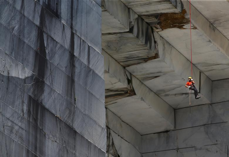 """A worker, known as a """"Tecchiaiolo"""", examines marble at the Cervaiole quarry on Monte Altissimo in the Apuan Alps, Tuscany, Italy, July 18. REUTERS/Alessandro Bianchi"""