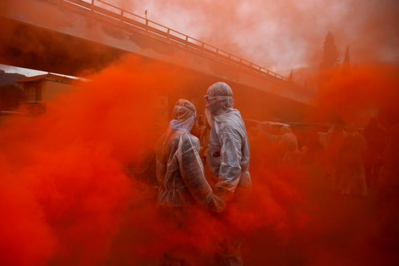 Two revellers are seen amid flare smoke as they celebrate Ash Monday by participating in a colorful flour war, a traditional festivity marking the end of the carnival season and the start of the 40-day Lent period until the Orthodox Easter, in the port town of Galaxidi, Greece, February 19. REUTERS/Alkis Konstantinidis