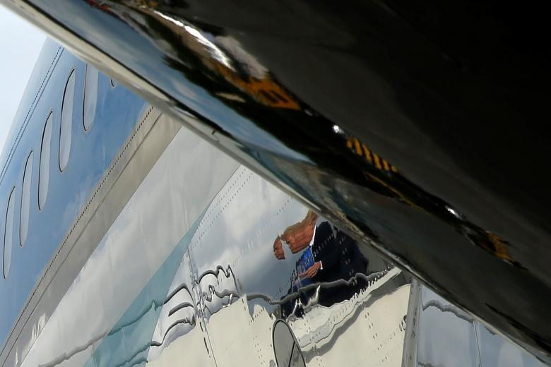 President Donald Trump is reflected in the fuselage as he boards Air Force One to depart as he returns home to the U.S. from Ninoy Aquino International Airport in Manila, Philippines November 14, 2017. REUTERS/Jonathan Ernst