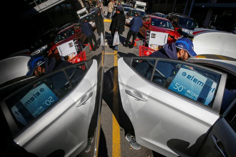 A man loads a television into his car during Black Friday shopping in the Brooklyn borough of New York City. REUTERS/Brendan McDermid