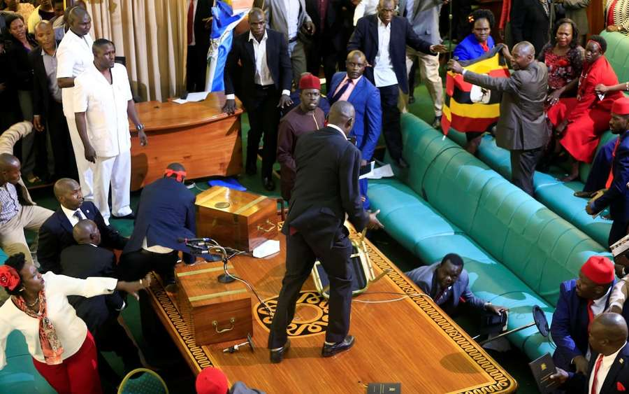Ugandan opposition lawmakers fight with plain-clothes security personnel in the parliament while protesting a proposed age limit amendment bill debate CREDIT: JAMES AKENA/REUTERS