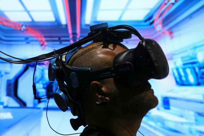 Pablo Holcer tests out a VR system made by Neurable that allows the user to control with their thoughts as the EEG headset interprets thoughts into actions in the VR environment at SIGGRAPH 2017 in Los Angeles, California, July 31, 2017. REUTERS/Mike Blake