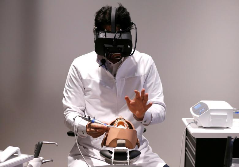A dentist wearing a VR headset, displaying X-ray photographs and other detailed information of a patient three dimensionally, demonstrates VR simulation program for dental surgeons (called WK2 Project), jointly developed by J. Morita Corp. and Realize Mobile Communications Corp., in Tokyo, Japan April 21, 2017. REUTERS/Issei Kato