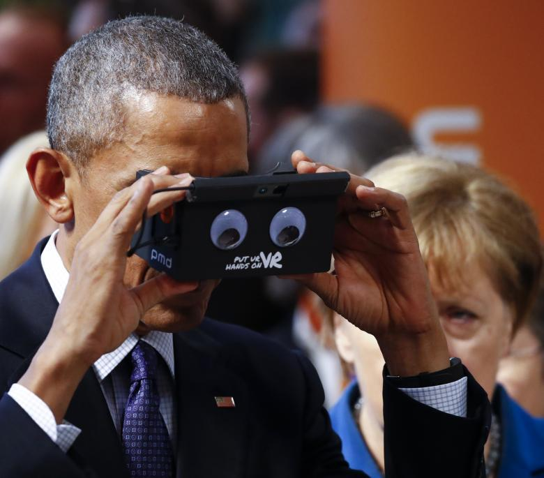 German Chancellor Angela Merkel stands with President Barack Obama as he tries the virtual reality device PMD during the opening tour of the Hannover Messe in Hanover, Germany. REUTERS/Kai Pfaffenbach
