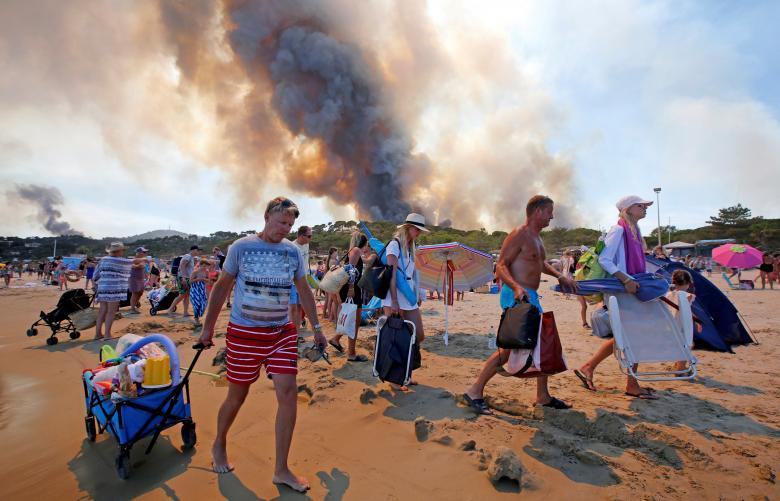 Tourists evacuate the beach as smoke fills the sky above a burning hillside in Bormes-les-Mimosas. REUTERS/Jean-Paul Pelissier