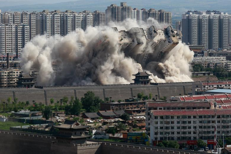 A building crumbles during a controlled demolition conducted to better protect the nearby ancient area of the city in Datong, Shanxi province, China, August 2016. China Daily/via REUTERS