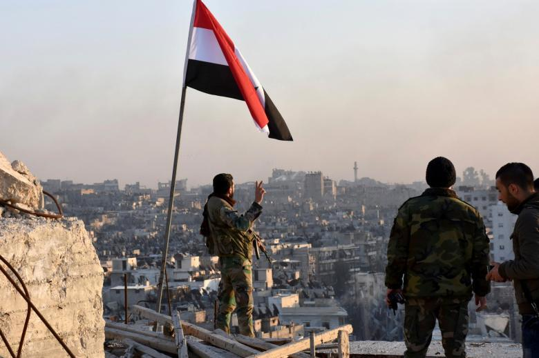 A Syrian government soldier gestures a v-sign under the Syrian national flag near a general view of eastern Aleppo after they took control of al-Sakhour neigborhood. SANA/Handout via REUTERS