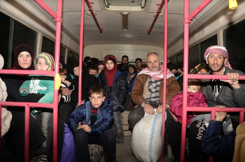 Syrians who evacuated the eastern districts of Aleppo ride a government bus in Aleppo. SANA/Handout via REUTERS