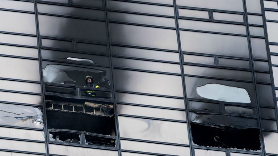A firefighter looks out the window of a damaged Trump tower apartment on April 7Craig Ruttle/AP
