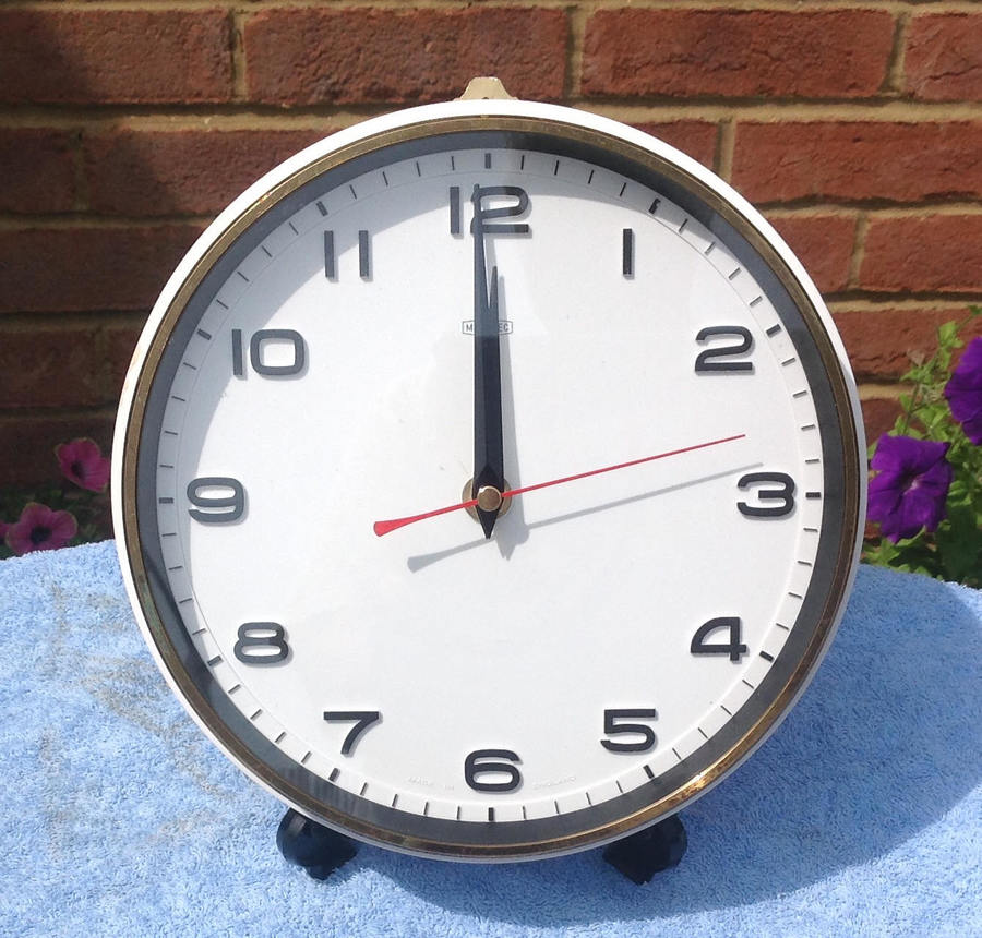 A white wall clock for the home or office made by Metamec in England in the 1960's. It is in good condition. The clock is white with black hands and a red second hand. The battery mechanism has been replaced with a new quiet quartz one with a sweep second hand.