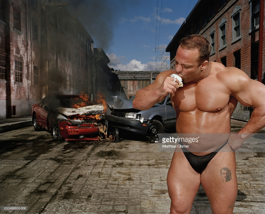 bodybuilder-eating-ice-cream-cone-car-collision-in-background-picture-id200486600-008
