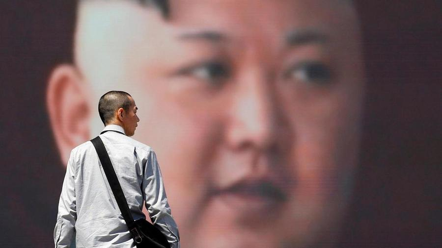 A-man-walks-past-a-street-monitor-showing-North-Korea-s-leader-Kim-Jong-Un-in-a-news-report-about-North-Korea-s-annou...