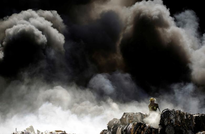 A firefighter works to extinguish the fire as it burns through a pile of old tires at a recycling centre in Ciudad Juarez, Mexico. REUTERS/Jose Luis Gonzalez
