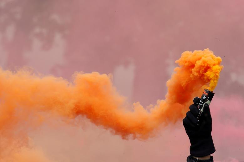 A protester holds a smoke safety flare during the May Day labour union march in Paris. REUTERS/Christian Hartmann