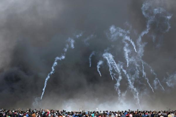 Tear gas canisters are fired by Israeli troops at Palestinian demonstrators during clashes at a protest demanding the right to return to their homeland, at the Israel-Gaza border in the southern Gaza Strip. REUTERS/Ibraheem Abu Mustafa