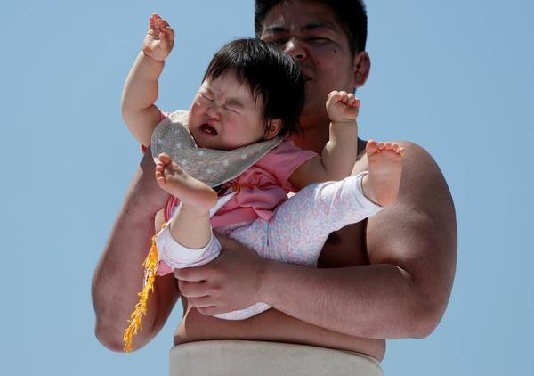 A baby cries in the arms of an amateur sumo wrestler during a baby crying contest at Sensoji temple in Tokyo, Japan. In the contest two wrestlers each hold a baby while a referee makes faces and loud noises to make them cry. The baby who cries the loudest wins. The ritual is believed to aid the healthy growth of the children and ward off evil spirits. 160 children took part in the event in this year, the organizer said. REUTERS/Issei Kato
