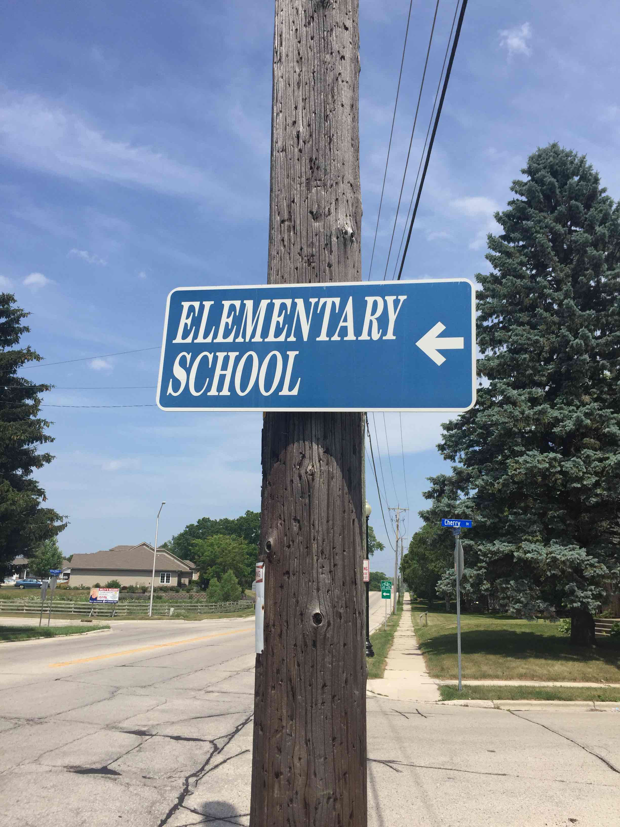 Photo of a sign for an elementary school with an arrow point towards the road, not the school