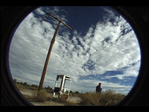 """""""Mojave Mirage"""" documents the phenomenon surrounding a lone phone booth in the Mojave Desert. The booth constantly received calls from all over the world, while people from all over the world began to travel there to see it live. The film captures a day in the life of the booth and the controversy spurred by its popularity."""