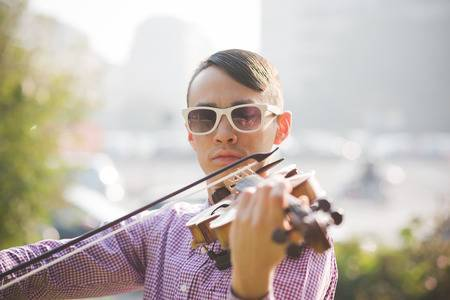 36673436-young-crazy-funny-musician-violinist-asian-man-in-town-outdoor-lifestyle.jpg?ver=6