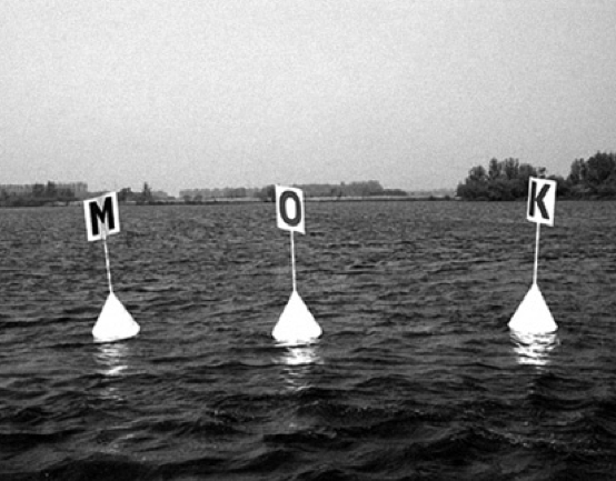 """""""The two-sided props, installed by designer Karel Martens and writer Kees't Hart, used a total of six letters (T/M, O/A, L/K) to power a """"word machine"""" capable of spelling 16 different Dutch words, from LOT (""""fate,"""" as in """"lottery"""") to TAL (""""number,"""" as in """"tally""""). Locked in this shrunken lexicon, bobbing in the chilly current, the buoys might have been mistaken for a physical version of the blinking cells in Conway's Life endgame—a kind of ultimate poem."""" (2007)"""