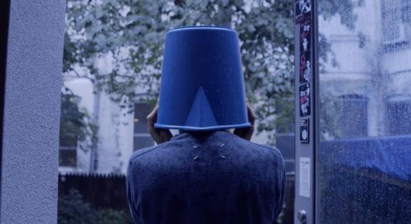 Ryuchi Sakamoto with a bucket on his head in the rain