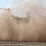An MV-22 Osprey kicks up dust and sand while landing
