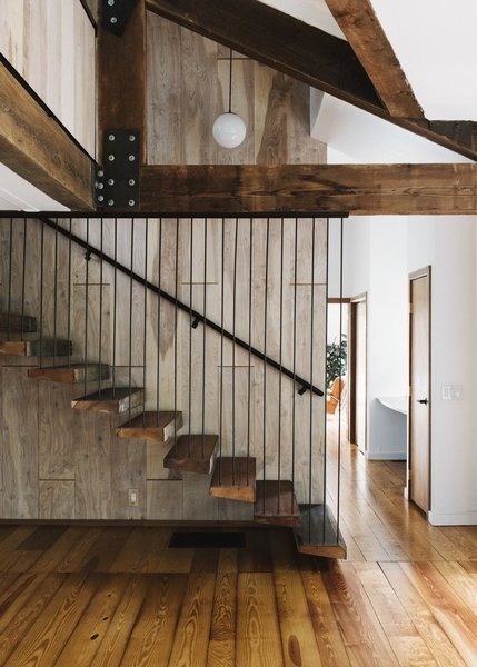 floating-against-birch-paneling-the-main-stair-incorporates-treads-salvaged-from-old-barn-wood.jpg