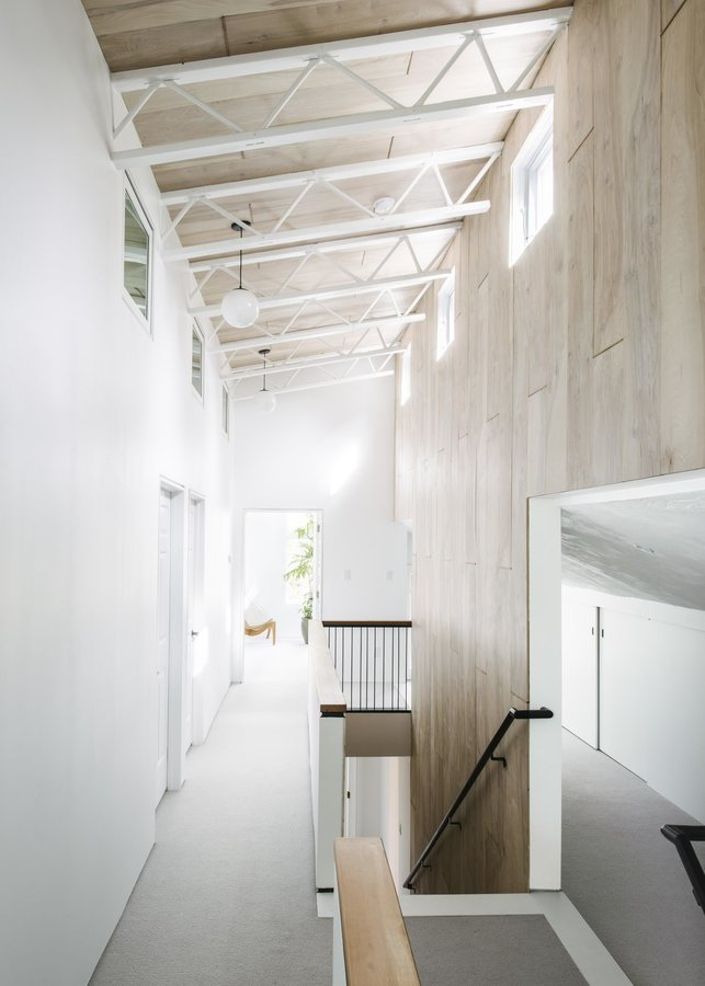 light-streams-into-the-upper-floor-of-the-addition-where-exposed-wood-and-steel-trusses-complement-the-existing-timber-struc...