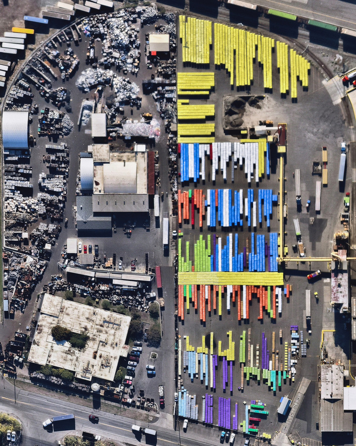 """Brightly colored shipping containers are stacked next to a scrap metal storage yard at the Port of Tacoma, Washington."""