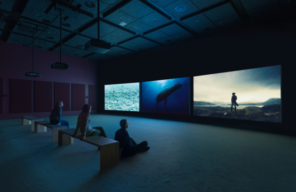 three_visitors_watching_a_three_channel_video_in_a_dark_screening_room-1024x665.png
