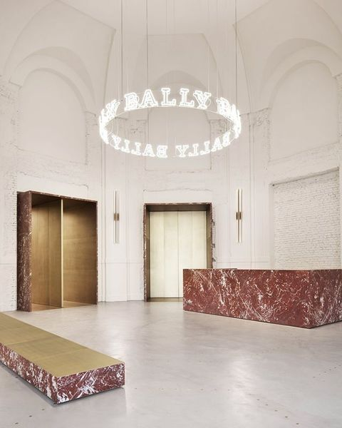 Gold doorways, amphitheatre-style display shelves and velvet furnishings appear in fashion label @bally's showroom in Milan,...