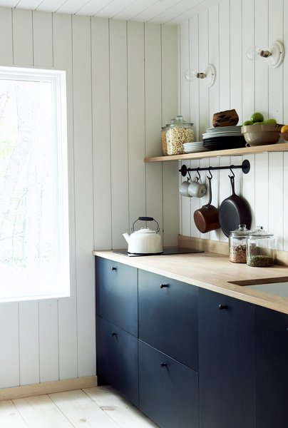 dark-cabinets-juxtapose-with-white-shiplap-in-this-simple-functional-kitchen-solar-power-supplies-the-electric-range-top.jpg