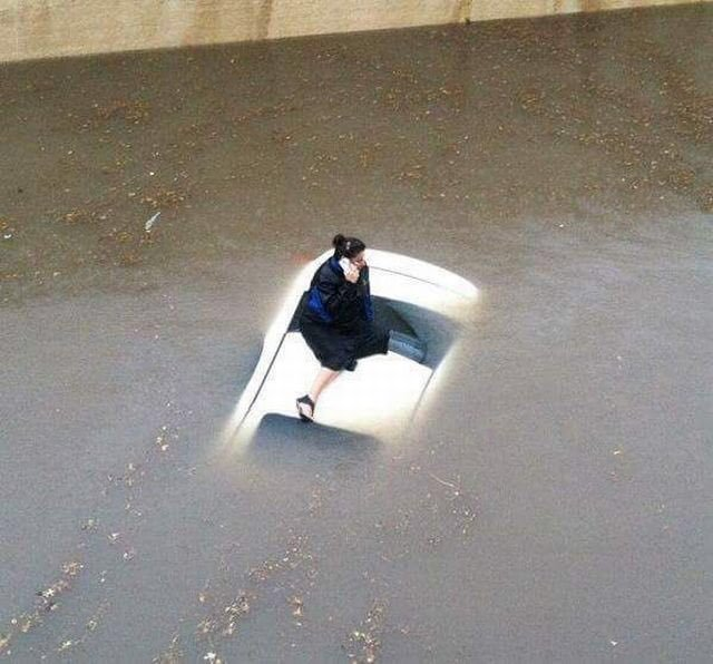 A woman on her phone on top of a car, surrounded by flood waters