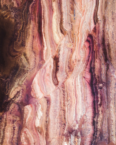 """""""This Overview shows colorful rock formations in the Sahara Desert, west of the town of Reggane, Algeria. The climate in this region is torrid and almost rainless, with an average annual rainfall of less than 0.4 inches (10 mm). In the summer, daytime temperatures are known to consistently reach 122°F (50°C), earning this area its nickname — the """"triangle of fire."""""""""""