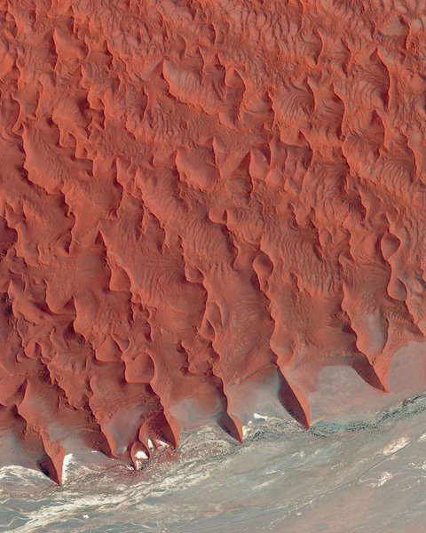 """""""Sossusvlei is a salt and clay pan located on the edge of the Namib Desert in Namibia. The reddish sand dunes seen in the top half of this Overview are among the tallest in the world, with many rising more than 656 feet (200 meters)."""""""