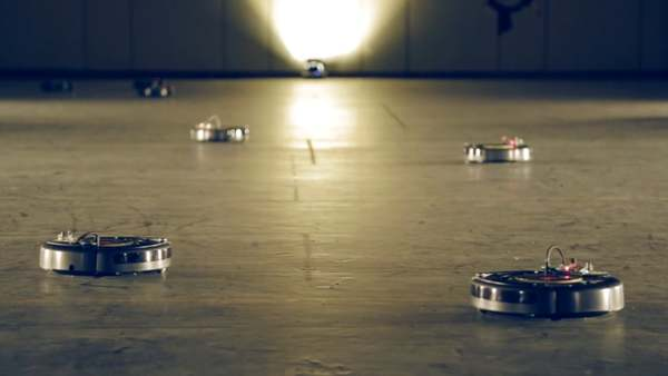 "A troop of robotic vacuum cleaners ""waltz"" with each other around a school gymnasium in this installation for the Biennale Interieur event in Kortrijk, Belgium. Interaction designer Pietro Leoni, of curator Joseph Grima's Geneva-based collective Space Caviar, programmed twelve Roomba vacuum cleaners to follow a routine created with choreographer Kostas Tsioukas."