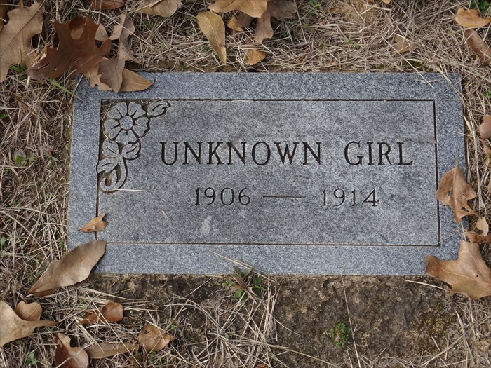 "The grave of an ""Unknown Girl"" is marked with a modern gray, granite headstone in historic Cottonwood Cemetery, Cottonwood, TX"