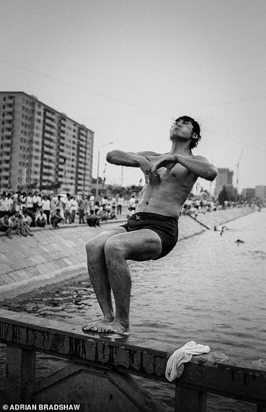 19747250-7571885-a_man_prepares_to_dive_into_a_canal_to_cool_off_in_beijing_in_19-a-178_1571157302710.jpg