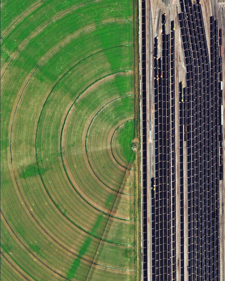 """Coal trains — some full, others empty — idle in a railyard next to a pivot irrigation circle in Alliance, Nebraska, USA. The city is located in the Powder River Basin — one of the world's largest coal-mining areas — and serves as a stopping point for trains en route to power plants in the Midwest and Southern parts of the country."""