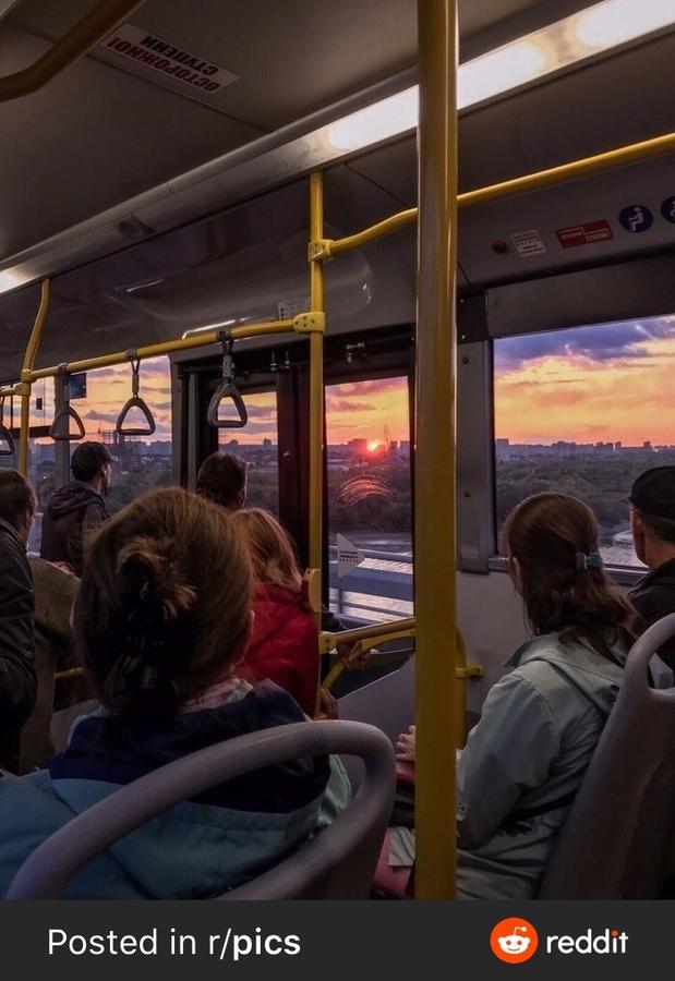 People on public transit watching a sunset