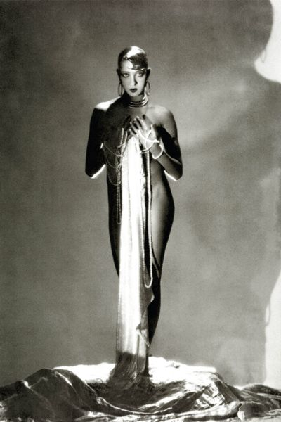 Josephine Baker, standing nude, with a long piece of fabric draped in front of her hanging from long stands of pearls which are wrapped around her hands, 1934. Photographed by George Hoyningen-Huene/Vanity Fair.