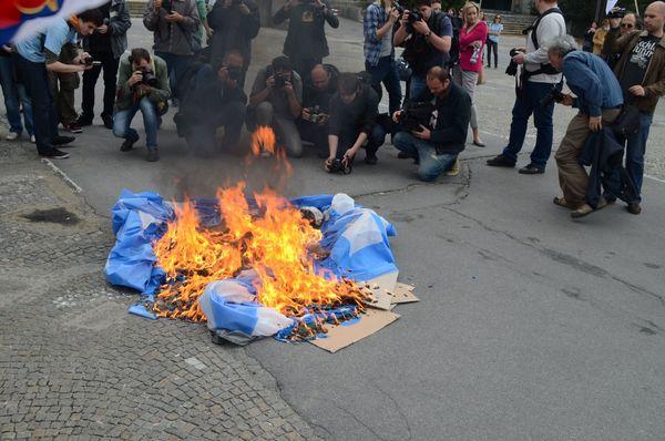 Photographers and Journalist Huddled around Burning Flag
