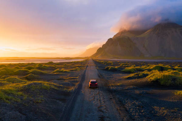 gravel-road-at-sunset-with-vestrahorn-mountain-and-a-car-driving-picture-id1192260535?k=6-m=1192260535-s=612x612-w=0-h=ft70y...